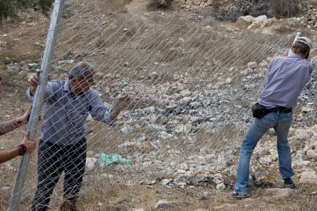 Palestino coloca la valla de su finca con la ayuda de un volutario estadounidense. Soldados israelíes y colonos la retiran contínuamente (A. Z.)