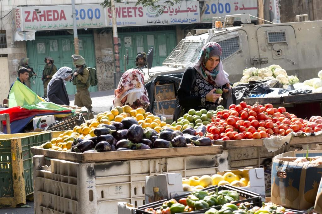 Una mujer palestina compra verduras en el centro de Hebrón junto a tanques y militares israelíes (A. Z.)