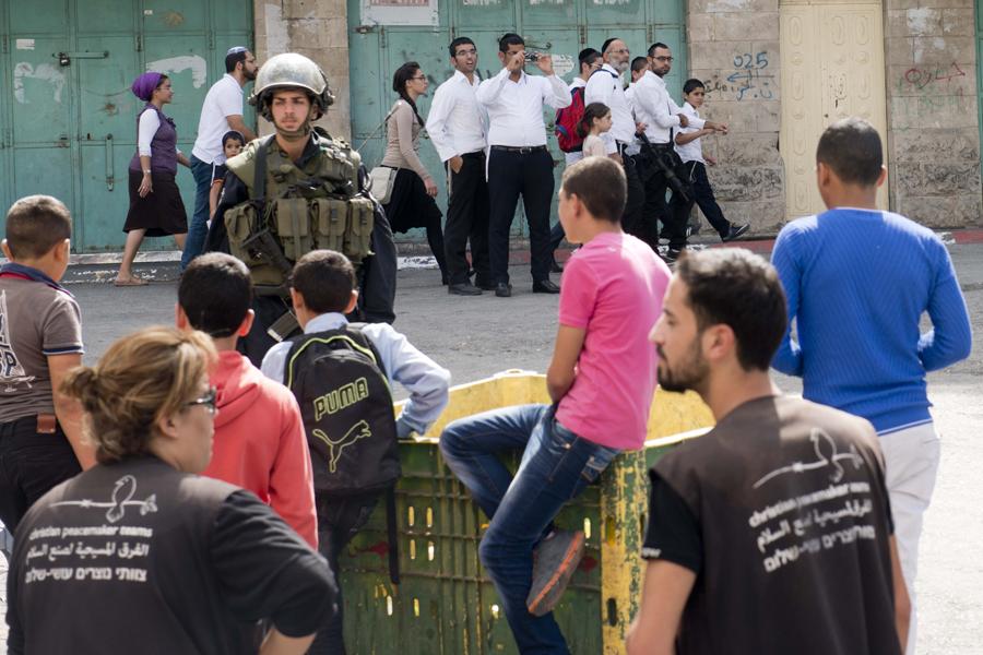 Los colonos de H2 son escoltados por militares israelíes el viernes cuando van a rezar mientras jóvenes palestinos y observadores internacionales contemplan la escena(A. Z.)